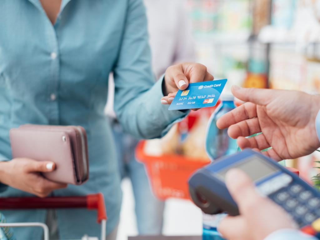 Woman paying for shopping with a chip and pin credit card.