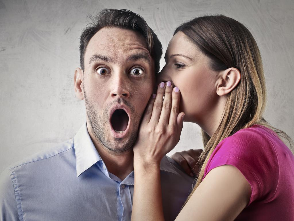 A woman telling a man a secret of how you can borrow a month's worth of money for free.